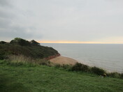 Orcombe Point from cliff top footpath with orange sky on the horizon