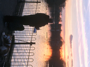 Artist with dog paints beautiful sunset over lake in Valentines Park