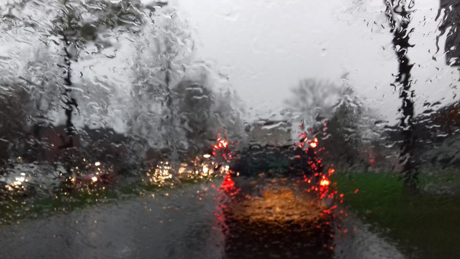 slecht weer vh verkeer, regendruppels op blad en autoruiten