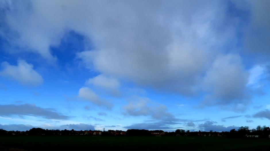 Zon, blauw en wolken om 12.00 uur