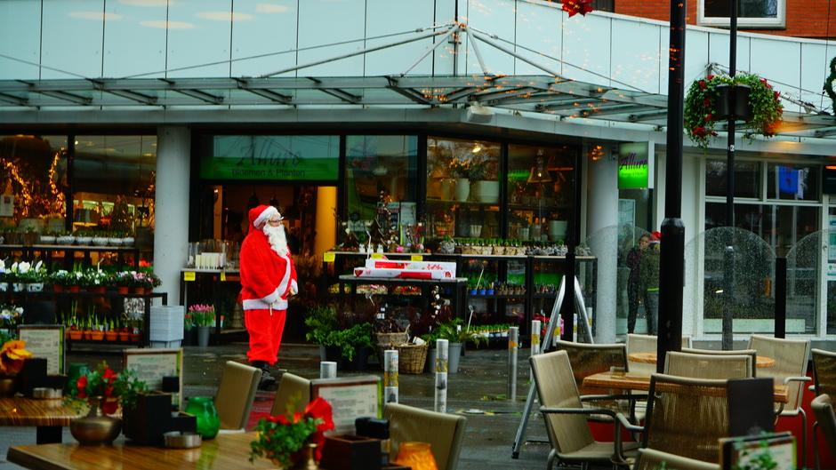 Kerstman zoekt beschutting tegen de regen.