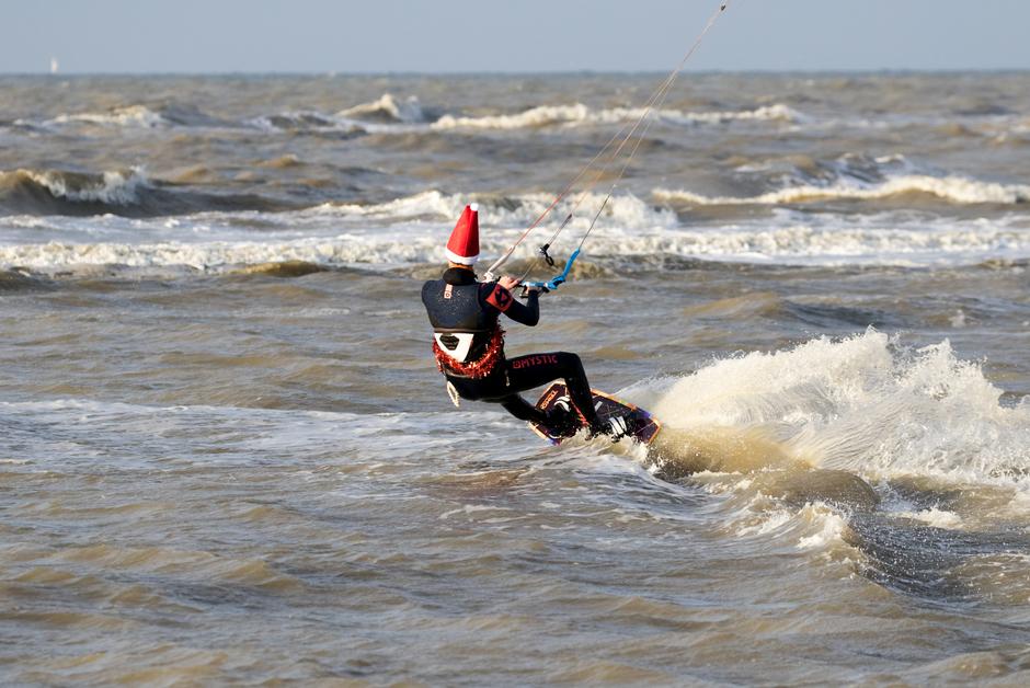 Kitesurfende Kerstman in de branding