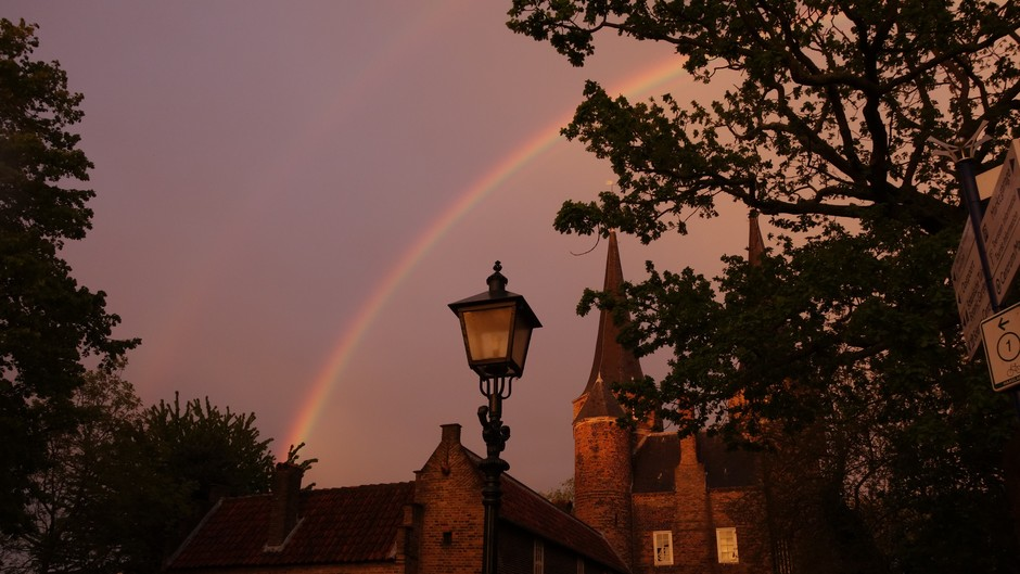 Dubbele regenboog en gloed van de ondergaande zon op de Oostpoort Delft