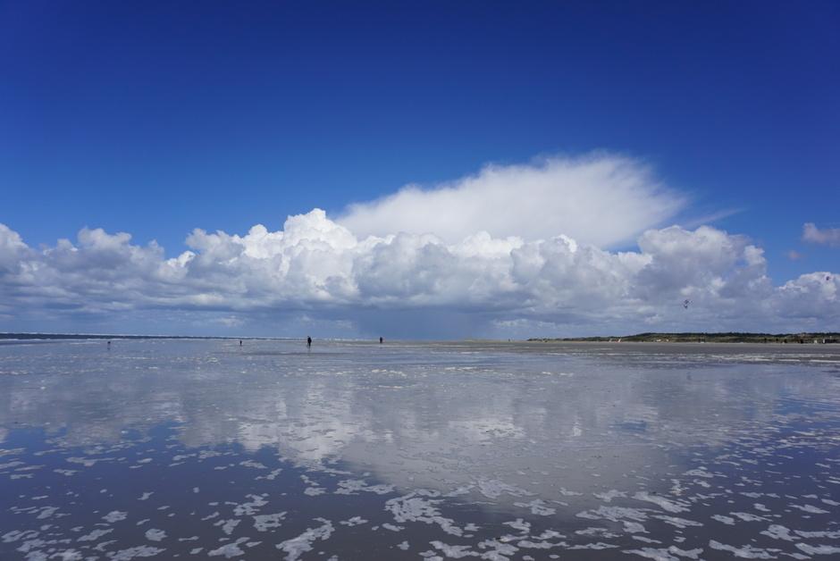 Wolk weerspiegeling op strand