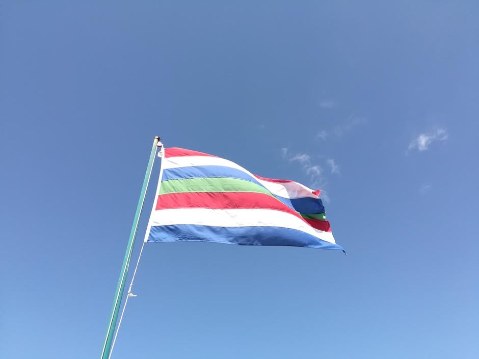Vlag Schiermonnikoog tegen blauwe lucht, weinig wind