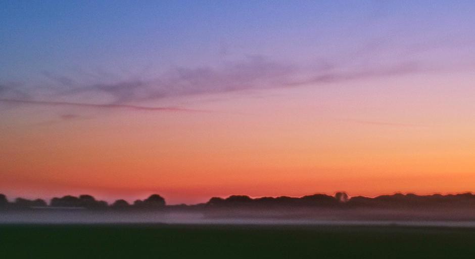 Kleurrijke zonsopkomst met een streepje mist