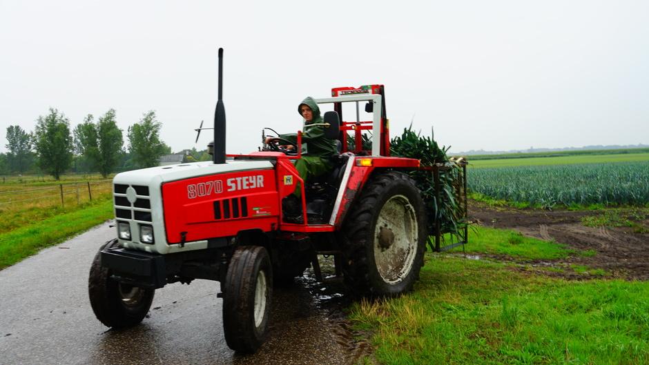 In regenkleding op de tractor
