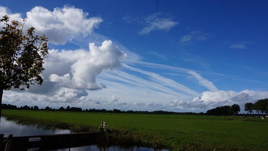 Buienwolken boven de polder met een zonnig blauwe lucht
