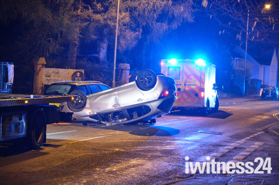 Upturned car closes road