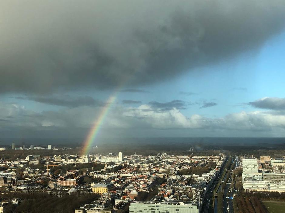 Donkere wolk met regenboog in Den Haag