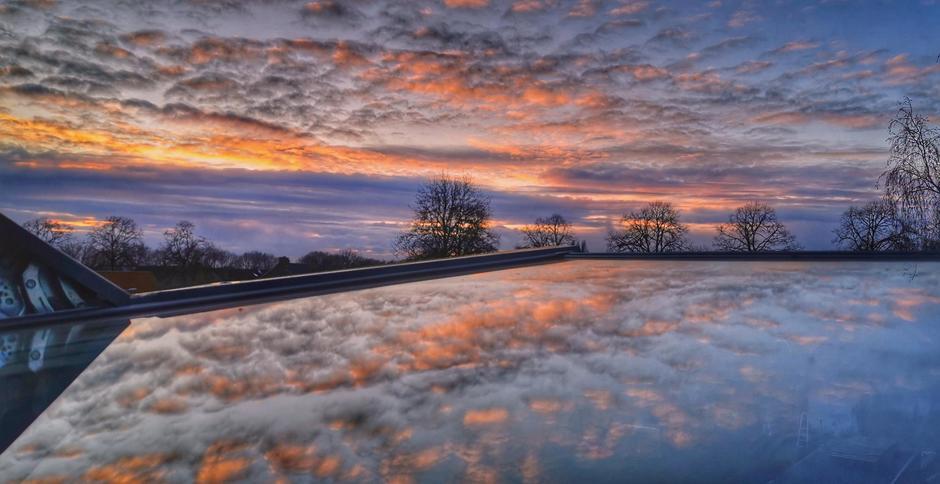 Zonsondergang met mooie reflectie in het zolderraam