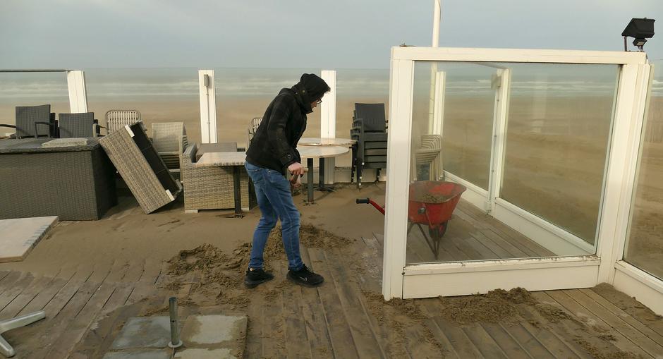 Zand van het terras halen.