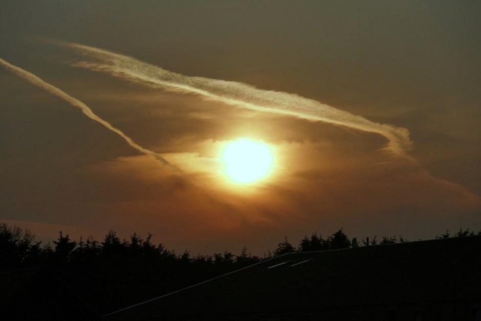 Zonsondergang met contrails