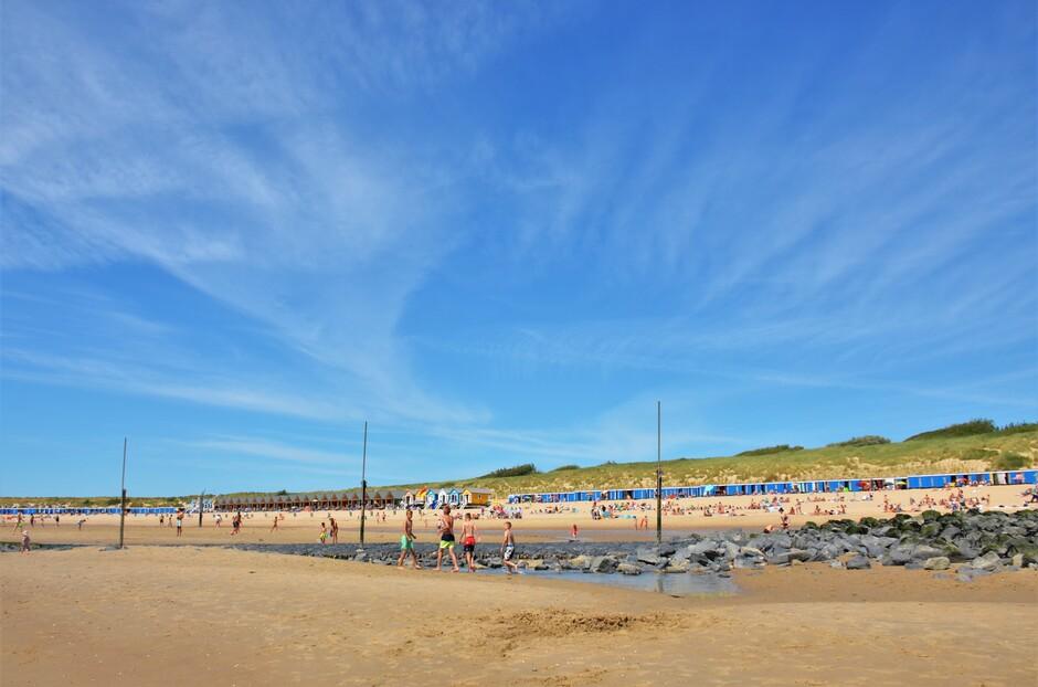 Zon en sluierbewolking aan het strand