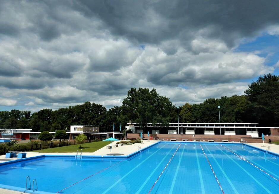 Zon en wolken boven een leeg zwembad.
