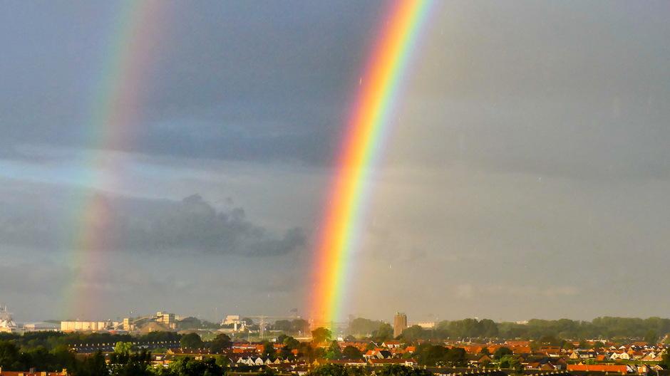 Dubbele regenboog in de ochtendzon.