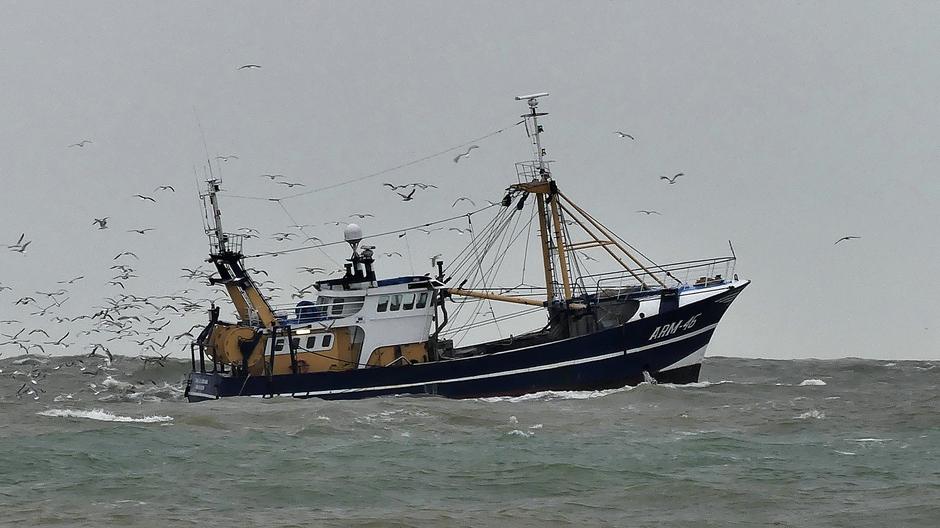 Vissersboot op onstuimige zee met sliert meeuwen
