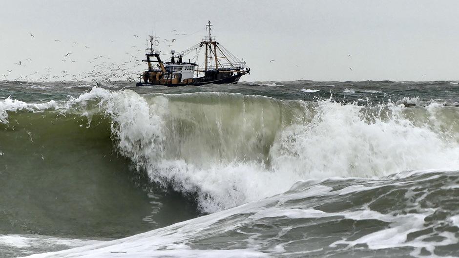 Vissersboot op een onstuimige zee een sliert meeuwen