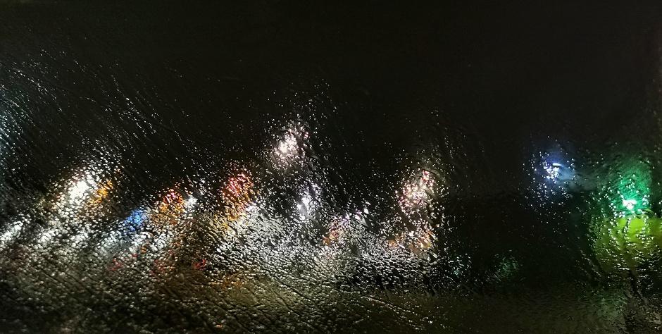 Regen op de autoruit midden in de nacht maakte van de lampen een soort kunstwerk