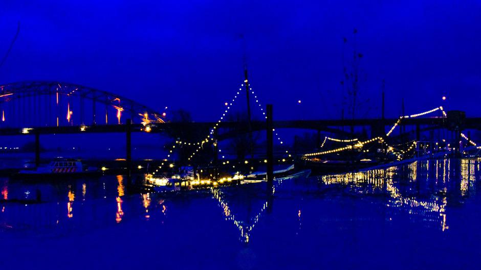Reflectie verlichting in regenwater tijdens het blauwe uurtje.