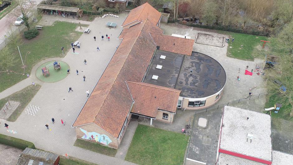 Heerlijk weer voor de spelende kinderen op het schoolplein in Opijnen
