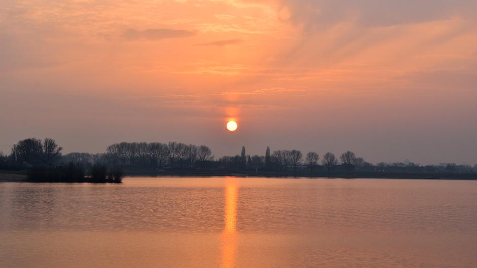 Zonnezuil tijdens zonsondergang boven de Rhederlaagse meren in Lathum
