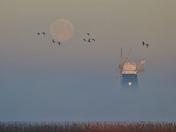Snow moon setting over Breydon water