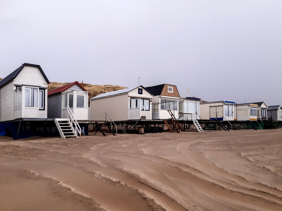 Grijs bewolkt verlaten strandhuisjes