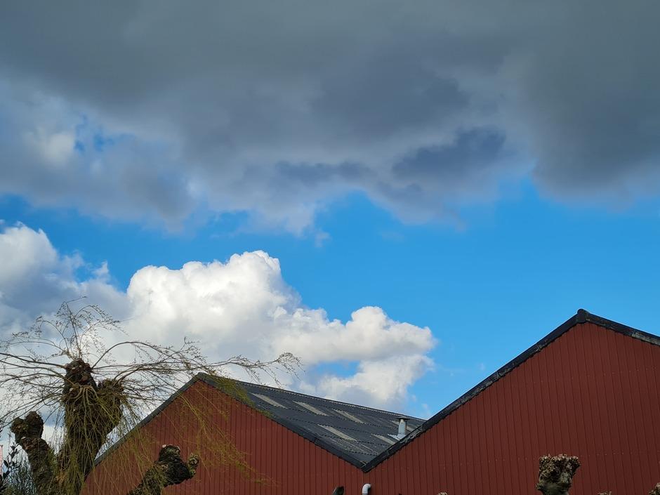 Donkere wolken zon knalblauwe lucht