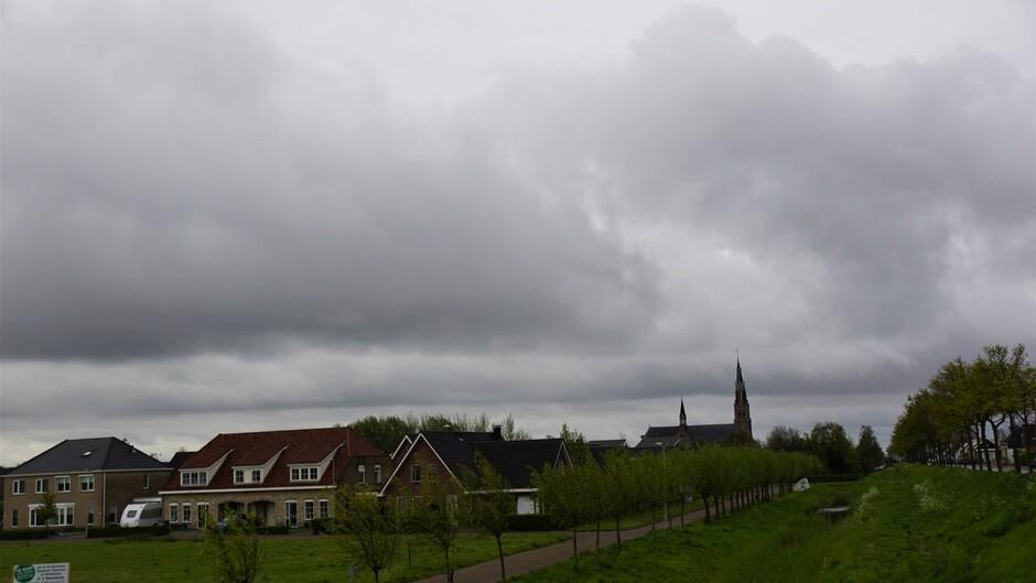 grijs bewolkt en buienlucht 13 gr af en toe een bui
