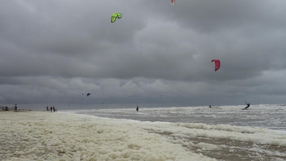 Donkere wolken, schuim en surfers Zandvoort
