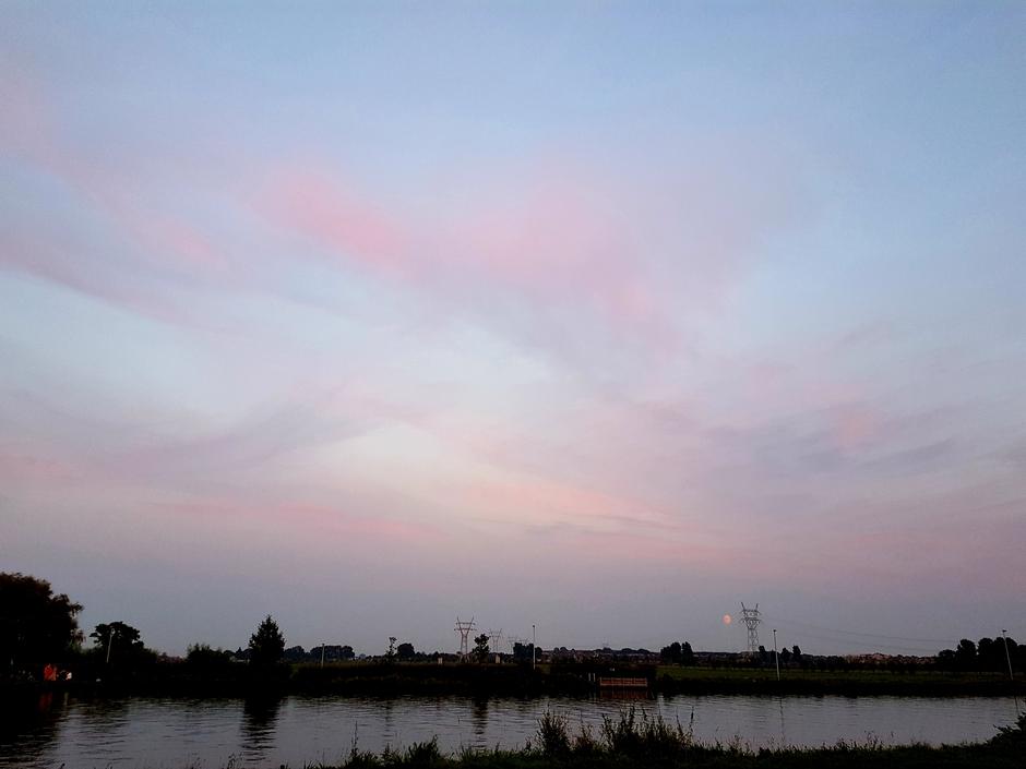 Wave wolken en een roze maan