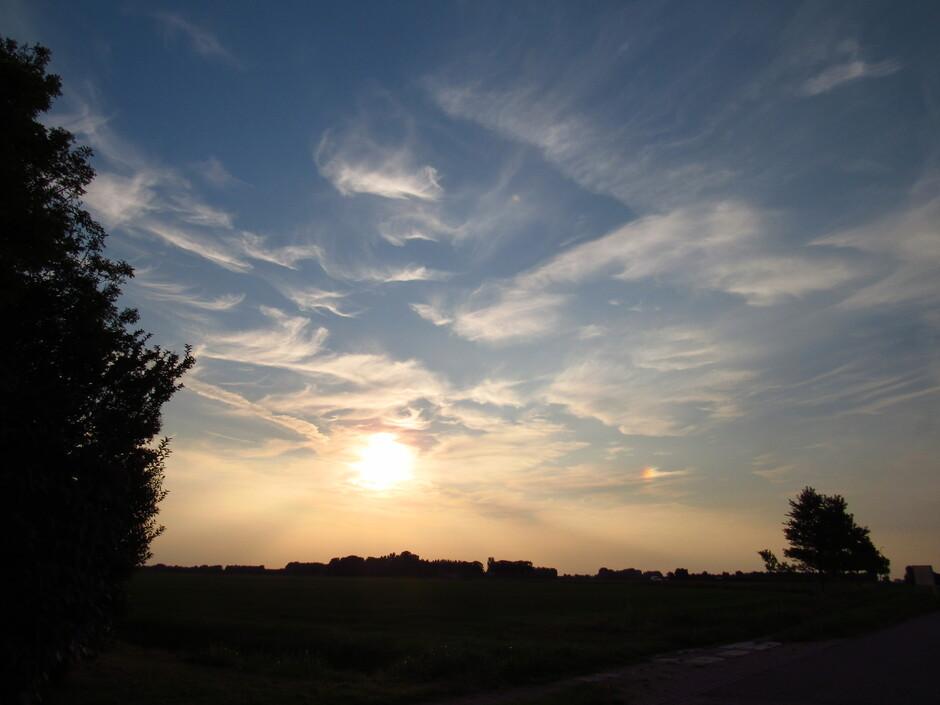 Voor zonsondergang met bijzon en vegen in de lucht bij Colijnsplaat