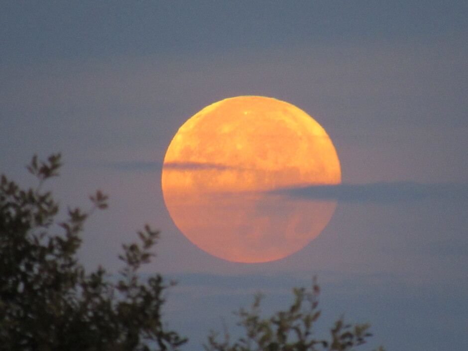 De bewolking trekt voorbij de mooi gekleurde maan waarna deze zal verdwijnen